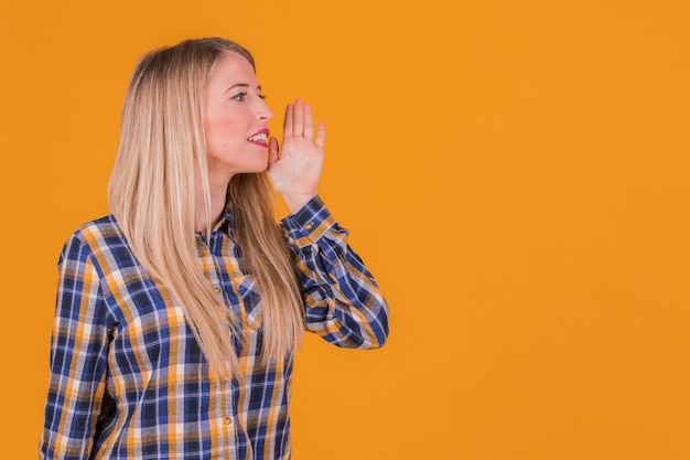Portrait of a young woman calling someone against an orange backdrop