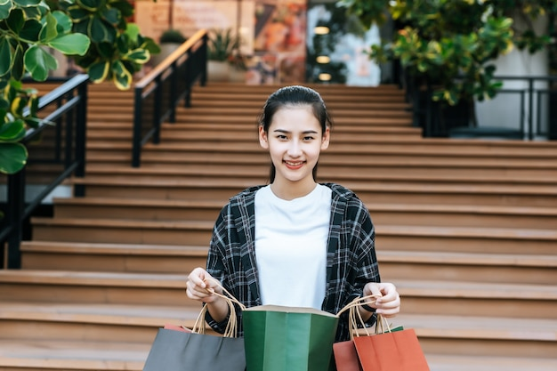 Portrait young woman carrying multiple shopping paper bag