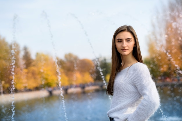 Portrait of young woman in casual wear posing near fountain outdoors. autumn in city