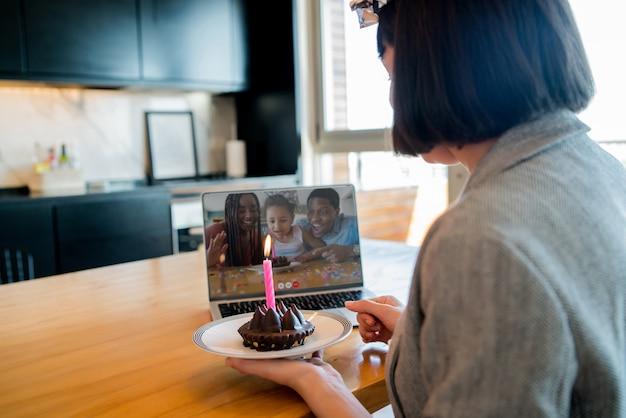Ritratto di giovane donna che celebra il compleanno in una videochiamata con laptop e torta da casa