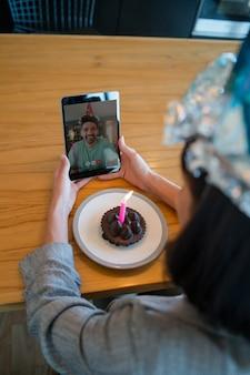 Ritratto di giovane donna che festeggia il suo compleanno in una videochiamata con tablet digitale e una torta a casa