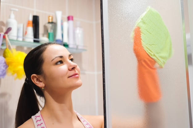 Portrait of young woman cleaning shower door