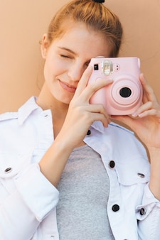 Portrait of a young woman clicking picture with pink instant camera against beige backdrop