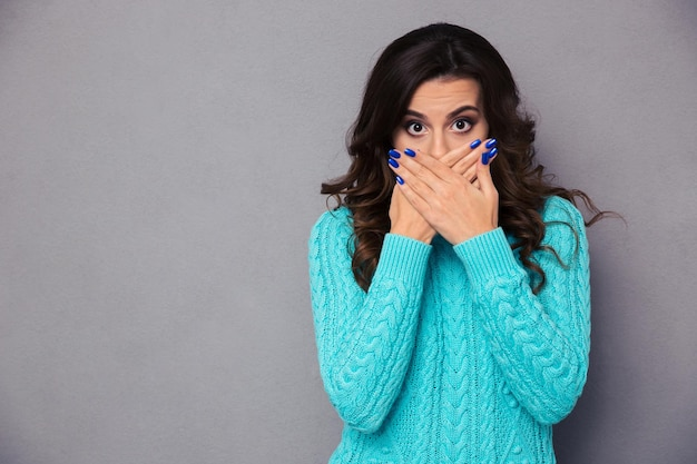 Portrait of a young woman covering her mouth with hands over gray wall and