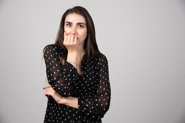 Ritratto di giovane donna che copre la bocca dietro l'articolazione.