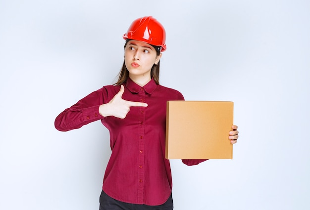 Portrait of a young woman in crash helmet pointing at small paper box .