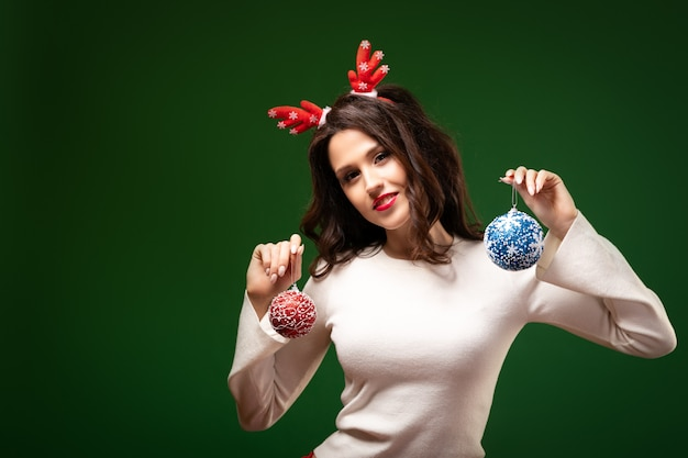 Portrait of a young woman in a deer rim and a white sweater charmingly smiles, poses and holds new year's balls in her hands