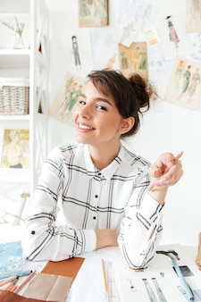 Portrait of a young woman designer drawing sketches