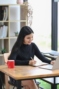 Дизайнер молодой женщины портрета с портативным компьютером пока сидя в творческом рабочем месте.