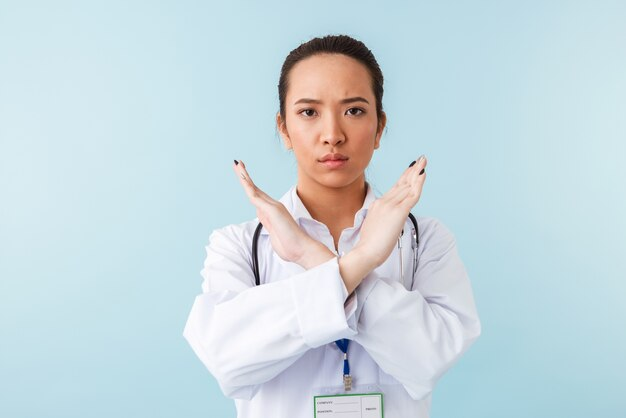 Portrait of a young woman doctor posing isolated over blue wall with stethoscope showing stop gesture.