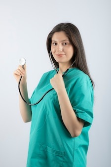 Ritratto di una giovane donna medico con stetoscopio in uniforme.