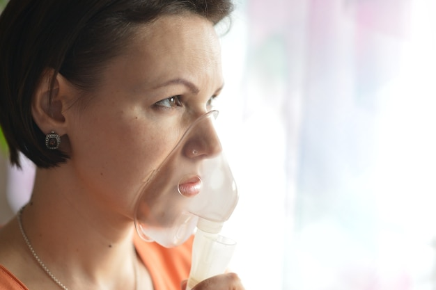 Portrait of a young woman doing inhalation at home