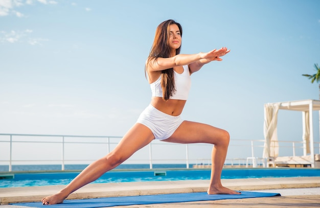 Portrait of a young woman doing stretching exercises on yoga mat outdoors in the morning