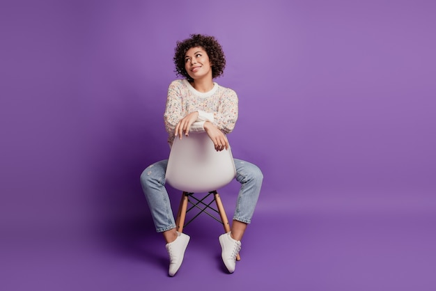 Portrait of young woman dream imagine look empty space sit chair on purple wall