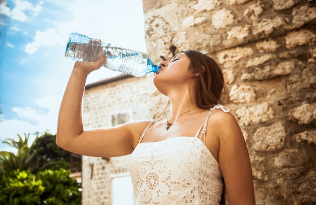 Portrait of young woman drinking water out of plastic bottle on street