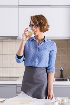 Portrait of a young woman drinking the wine while preparing the pizza