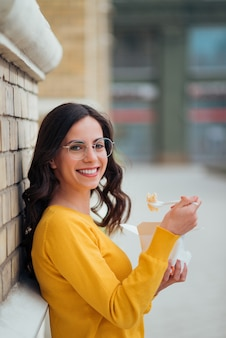 Portrait of a young woman eating from takeaway box outdoors, leaning on a wall and smiling at camera.