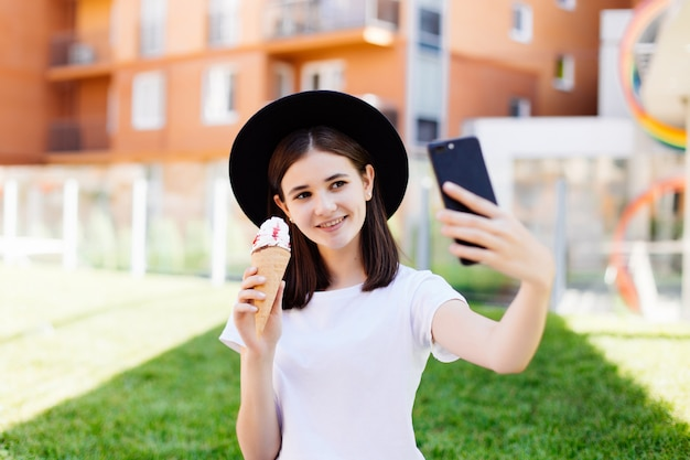 Portrait of young woman eating ice cream and taking selfie photo on camera in summer street.