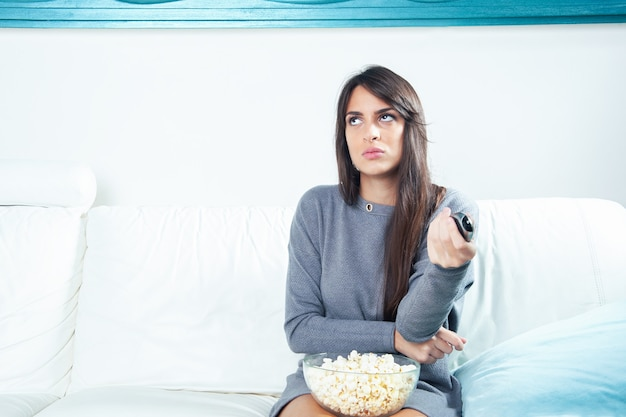 Portrait of a young woman eating popcorn while watching tv at home