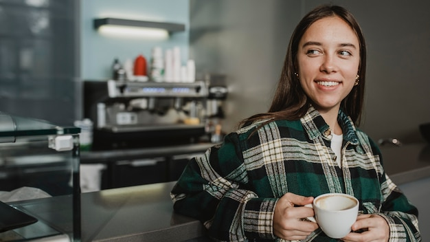Portrait of a young woman enjoying coffee