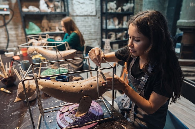 Portrait of young woman enjoying favorite job in workshop. potter carefully works on the clay whale