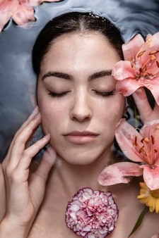 Portrait of young woman enjoying floral treatment