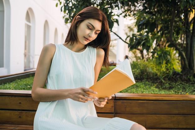 Ritratto di giovane donna che gode del tempo libero e legge un libro seduti all'aperto. concetto di stile di vita.