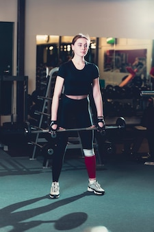 Portrait of a young woman exercising with barbell