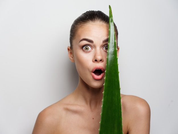 Portrait of young woman face makeup cosmetology clean skin green aloe leaf