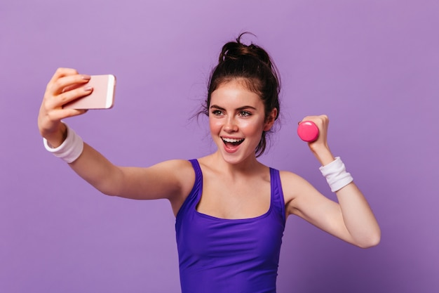 Portrait of young woman in fitness top holding pink dumbbell and taking selfie on purple wall