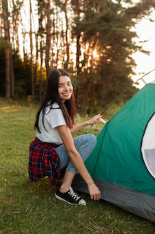 Portrait of young woman fixing tent