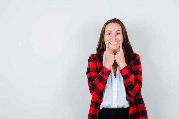 Ritratto di giovane donna che forza un sorriso sul viso con le dita in abiti casual e che sembra allegra vista frontale