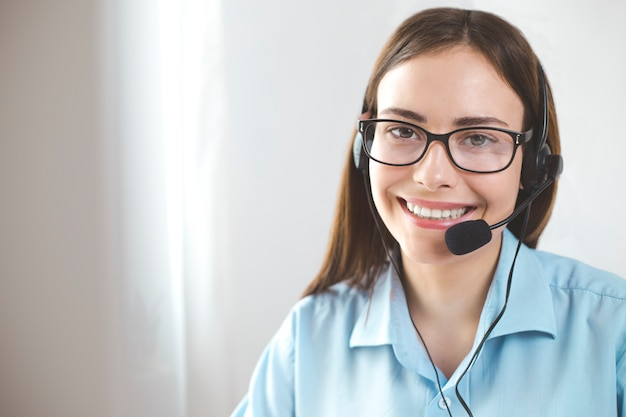 Portrait young woman friendly operator working in a call centre.