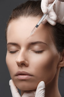 Portrait of young woman getting cosmetic injection