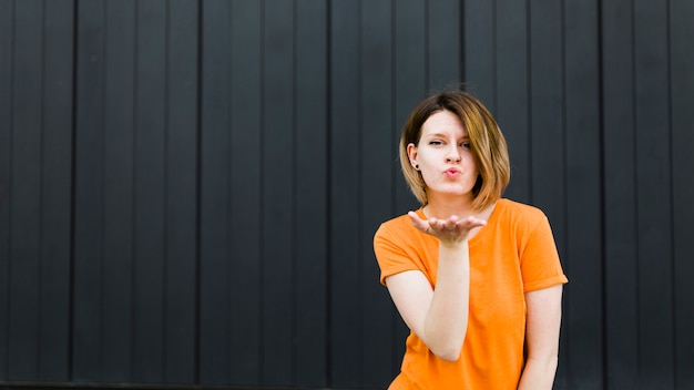 Portrait of a young woman giving flying kiss