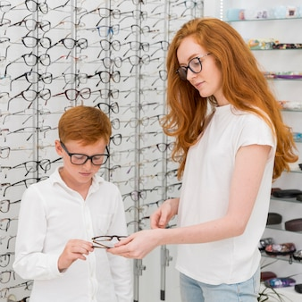 Portrait of young woman giving spectacle to her brother at optics store