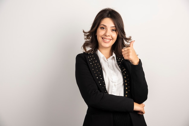 Portrait of young woman giving thumbs up.