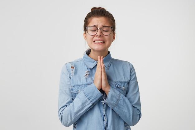 Ritratto di giovane donna con gli occhiali sta con gli occhi chiusi, le mani giunte davanti a lei