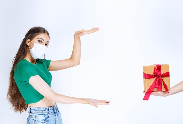 Ritratto di giovane donna in camicia verde in piedi mentre qualcuno le fa un regalo.