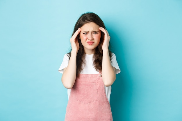Ritratto di giovane donna che fa smorfie da dolorosa emicrania, accigliata e toccante la testa, con mal di testa, in piedi su sfondo blu.