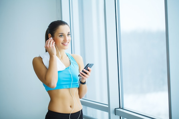 Portrait of young woman in gym posing with towel on neck and listening to music using earphones and smartphone