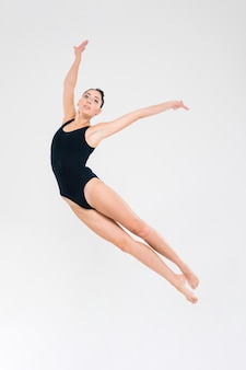 Portrait of young woman in gymnast suit doing acrobatic stunt isolated on a white wall