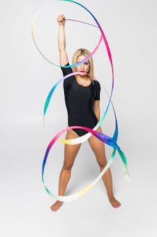 The portrait of young woman gymnast training calilisthenics exercise with ribbon. art gymnastics concept.