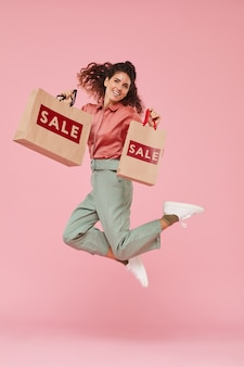 Portrait of young woman happy with her successful shopping she jumping against the pink background