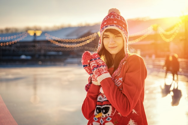 Portrait of a young woman in a hat on the ice rink
