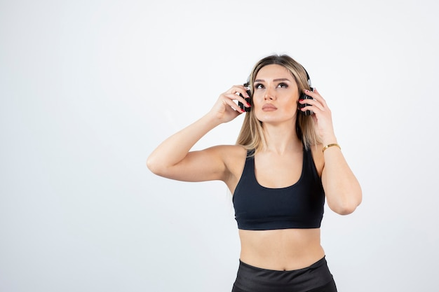 Portrait of young woman in headphones posing on white wall.