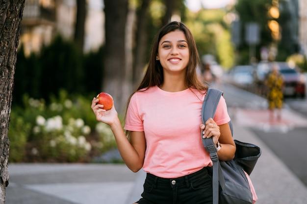 Ritratto di una giovane donna con mela su uno sfondo di strada