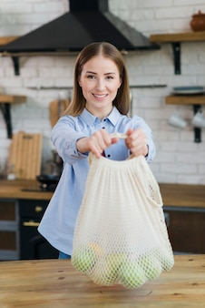 Portrait of young woman holding bag with organic fruits