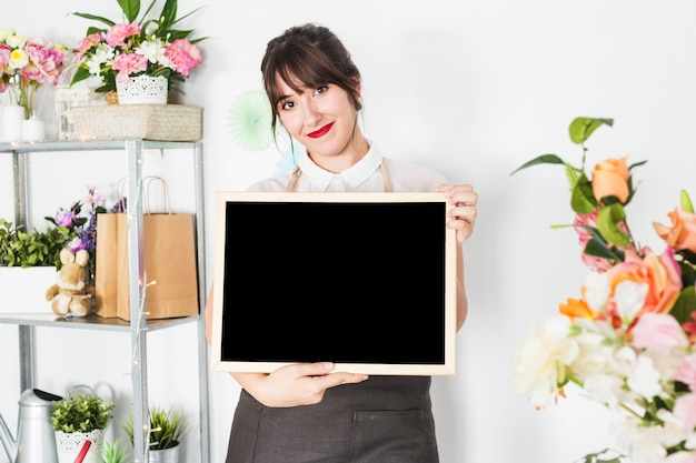 Portrait of a young woman holding blank slate