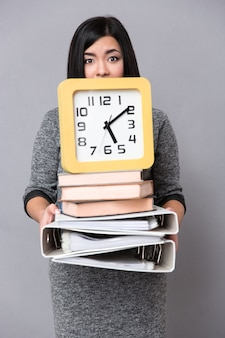 Portrait of a young woman holding books, folders and wall clock over gray wall